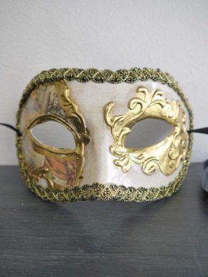 Krämfärgad prydnadsmask med gulddekor. Besök Blickfång.se
