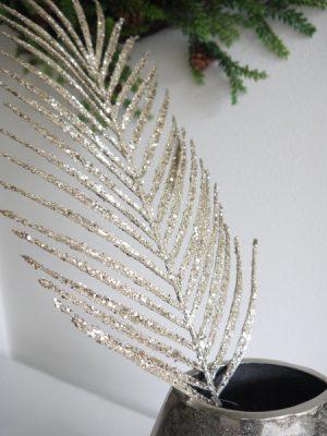 Blad i guld och glitter för dekoration i en vas