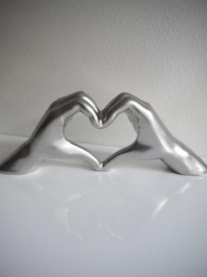 Händer i silver formade som hjärta. Besök Blickfång.se