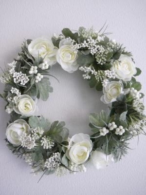 Konstgjord krans med vita blommor. Besök Blickfång.se